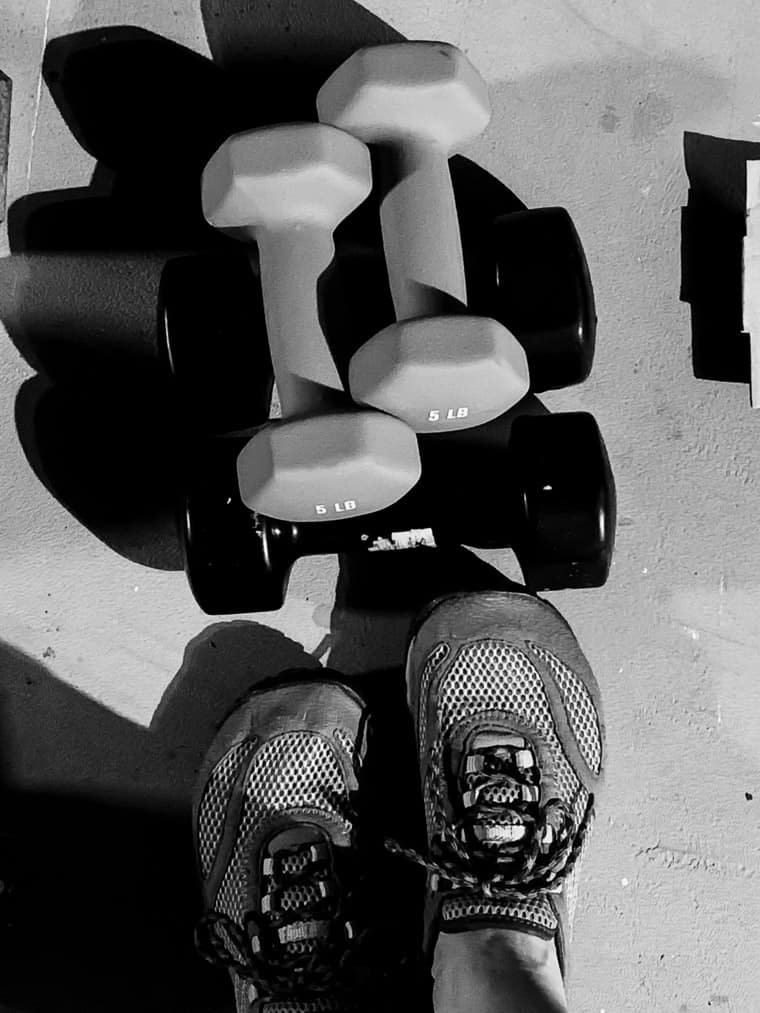 Looking down at 2 sets of weights with shoes showing in black and white