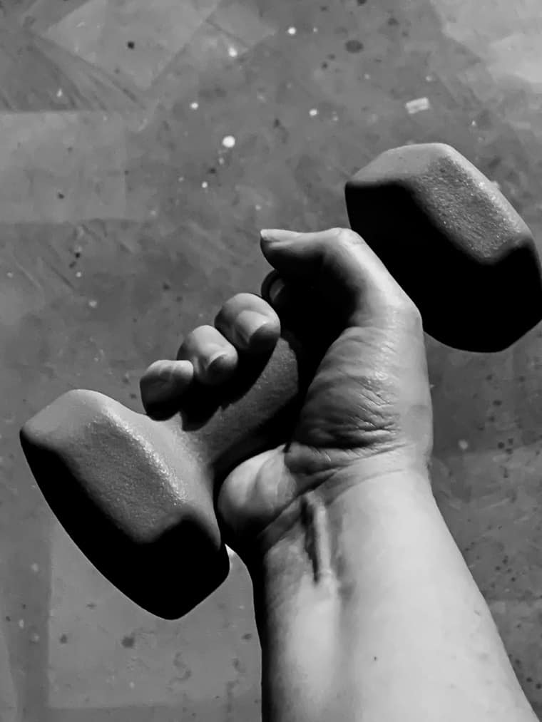 A hand holding a weight in black and white