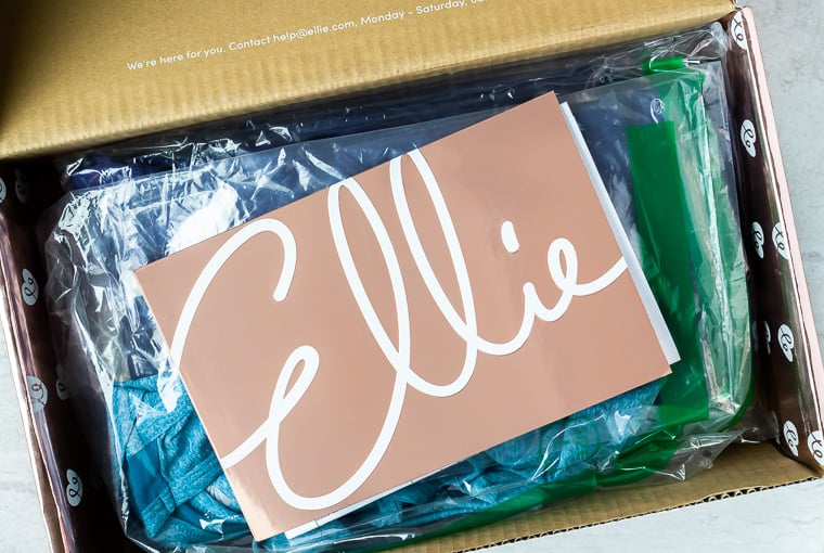 An open box with an Ellie envelope on top and clear bags with athletic wear in them