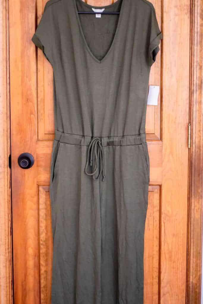 Caslon v-neck blousan jumpsuit in olive on a hanger over a wood door