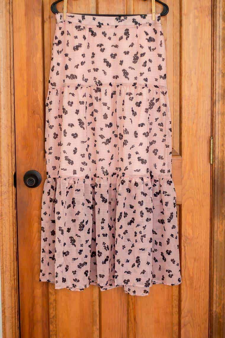 Leith tiered maxi skirt on a hanger over a wood door