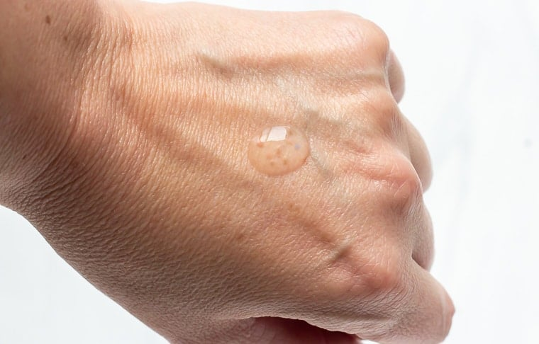 A drop of clear serum with pink and blue molecules in it on the back of a hand