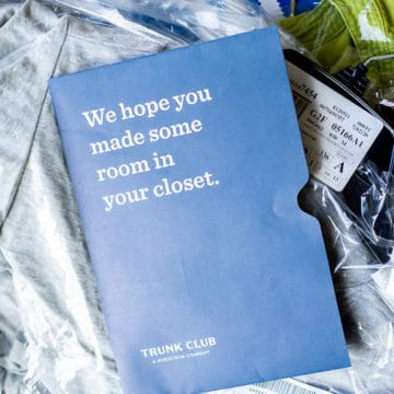 Opened trunk from nordtrom trunk club with the invoice on top of bags of clothing
