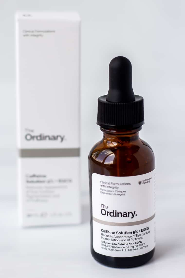 A bottle of The Ordinary Caffeine Solution 5% + EGCG with the box behind it on a white background