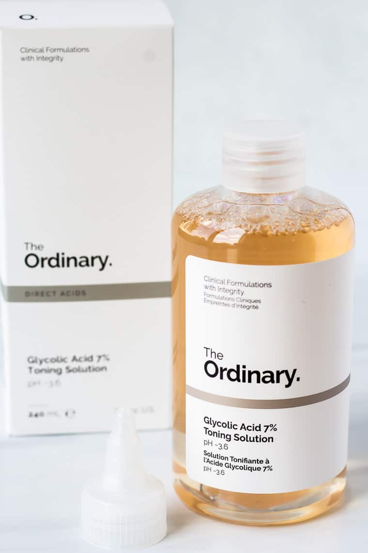 Abottle of The Ordinary Glycolic Acid 7% Toning Solution with the cap next to it and the bottle behind it on a white background