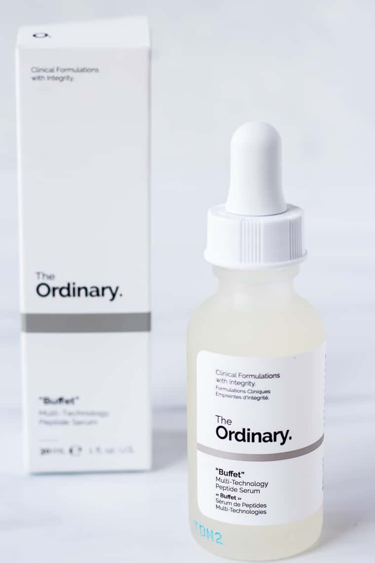 A Bottle of The Ordinary Buffet with the box behind it on a white background