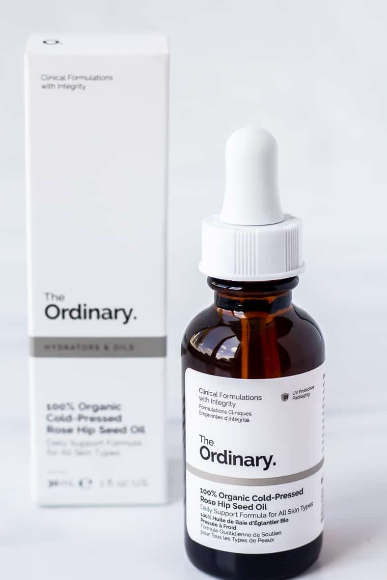 A bottle of The Ordinary 100% Organic Cold Pressed Rose Hip Seed Oil with the box behind it on a white background