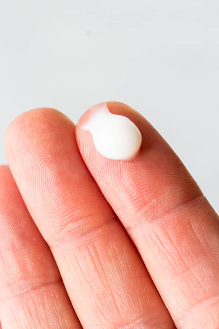 A white blob of The Ordinary Squalane Cleanser on finger tips