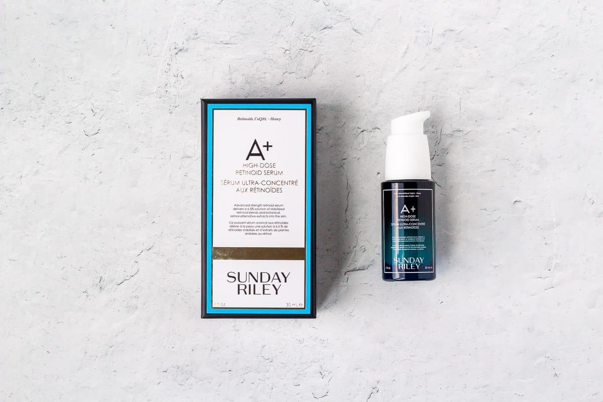 Sunday Riley A+ High Dose Retinol Serum tube next to it's box on a white background