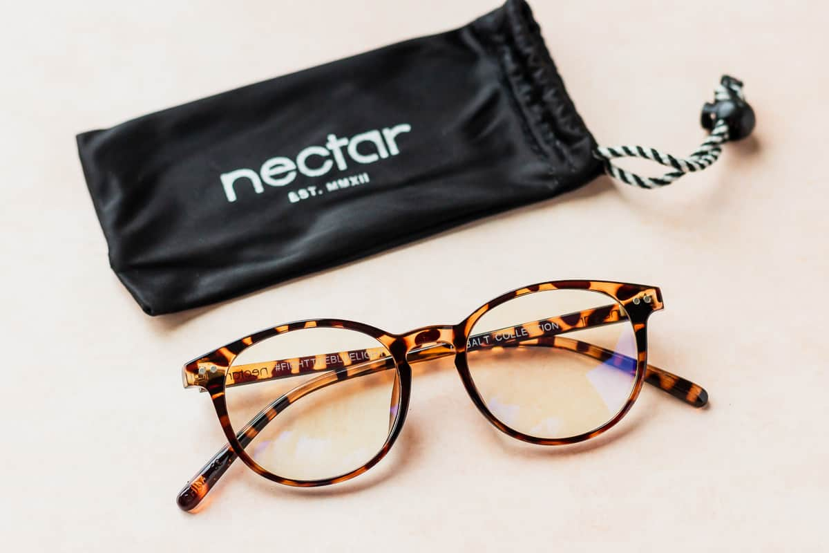 Nectar Blue Light Glasses and it's felt case on a peach background