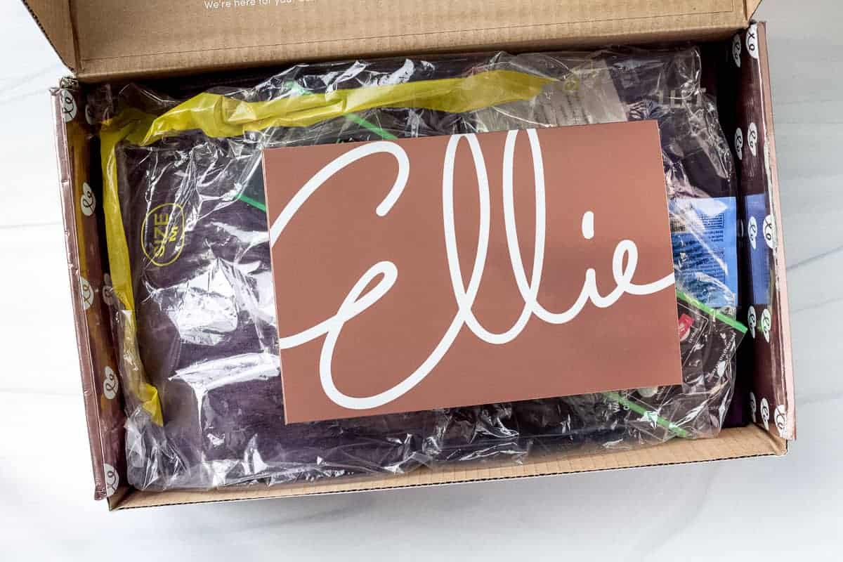 Opened Ellie subscription box with an insert card on top of the items
