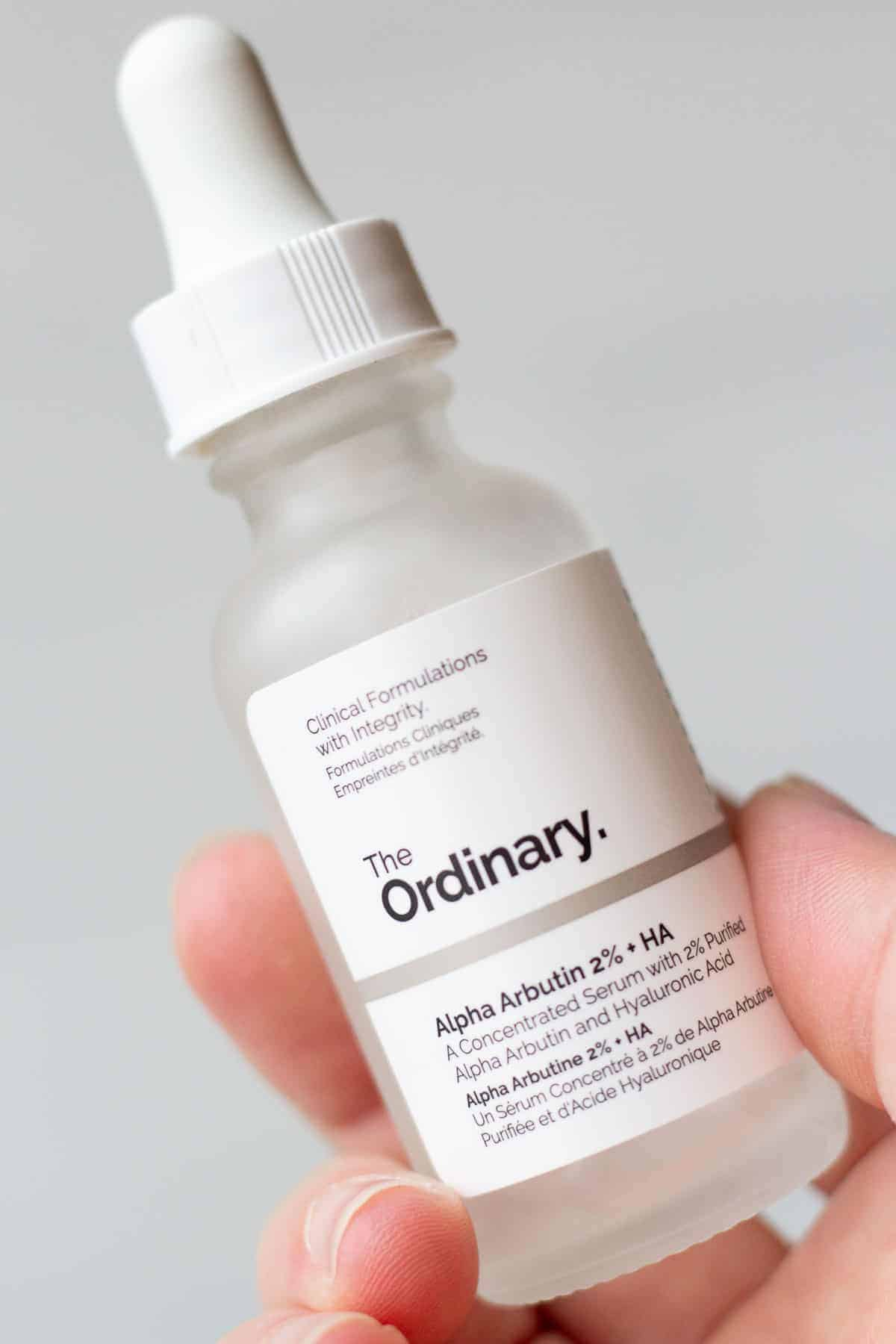A hand holding a bottle of The Ordinary Alpha Arbutin