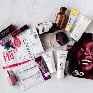 All of the beauty products and samples from the October 2020 Allure Beauty Box laid out on a white background