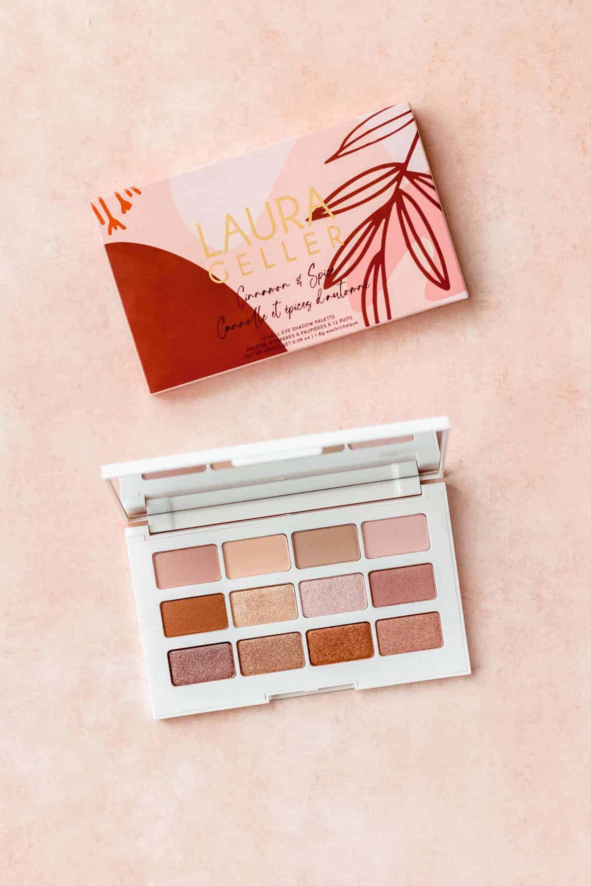 Laura Geller Cinnamon + Spice Eyeshadow Palette opened with packaging on a peach background
