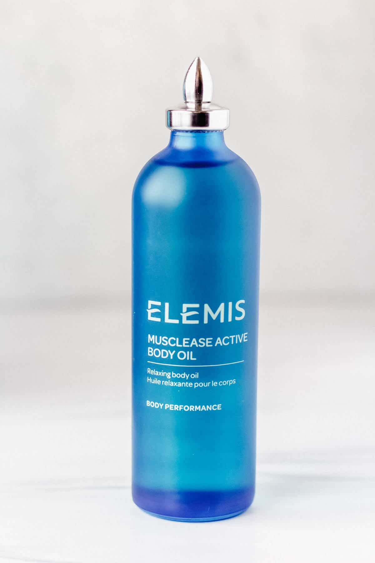 Elemis Muclease Active Body Oil bottle on a gray background