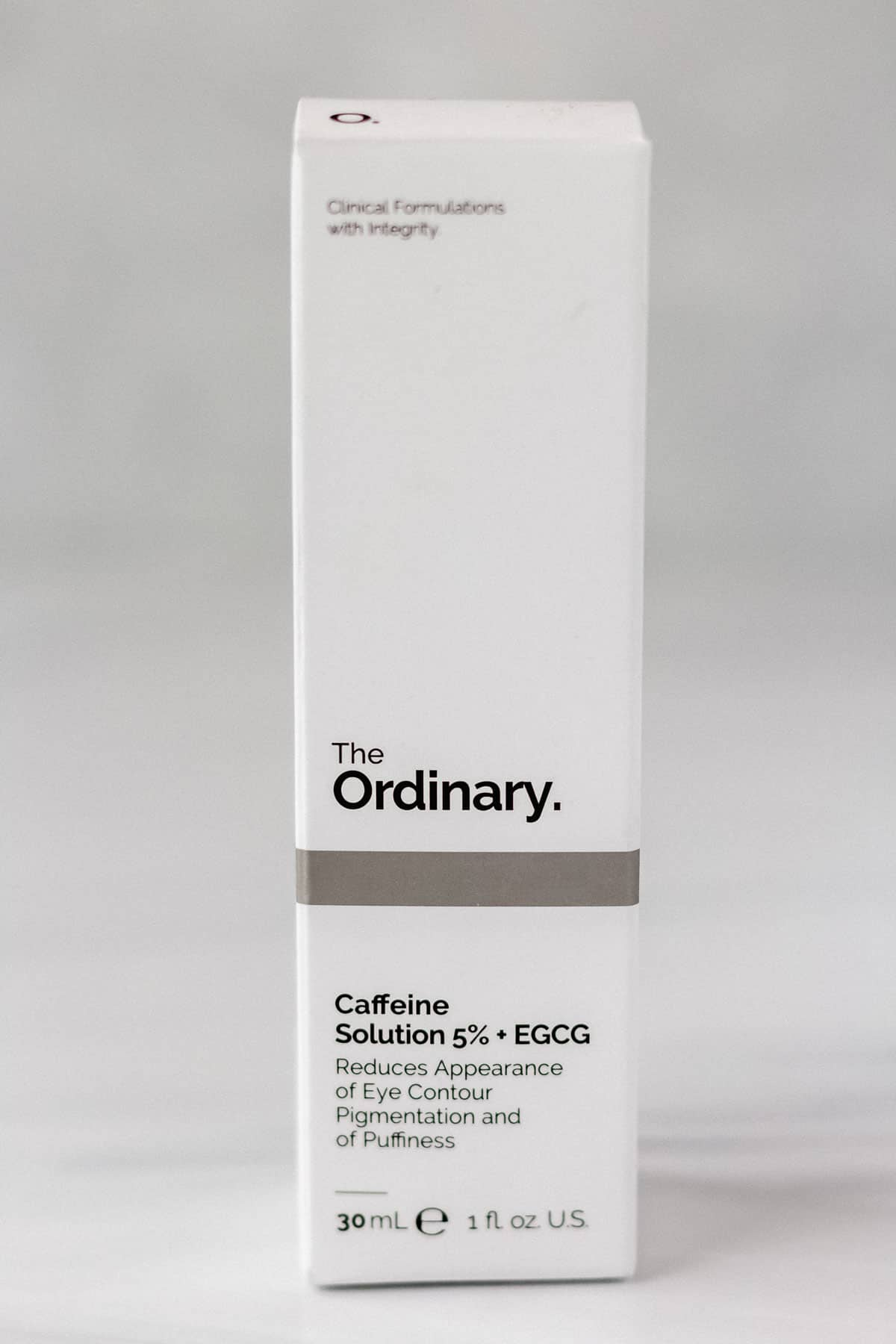 A box of The Ordinary Caffeine Solution 5% + EGCG on a gray background