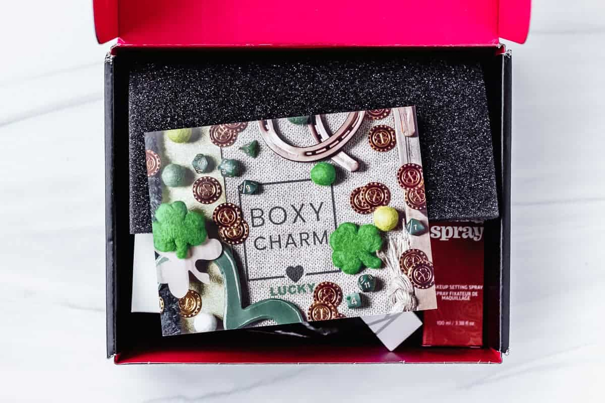 Opened March 2021 Boxycharm Base Box on a white background with the insert card on top of the beauty products inside
