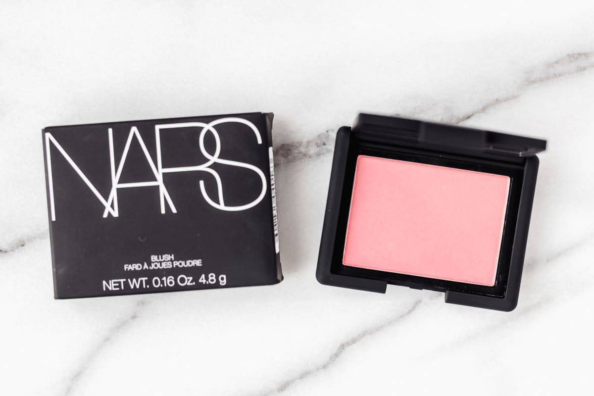 NARS Blush in Deep Throat opened next to its box on a marble background