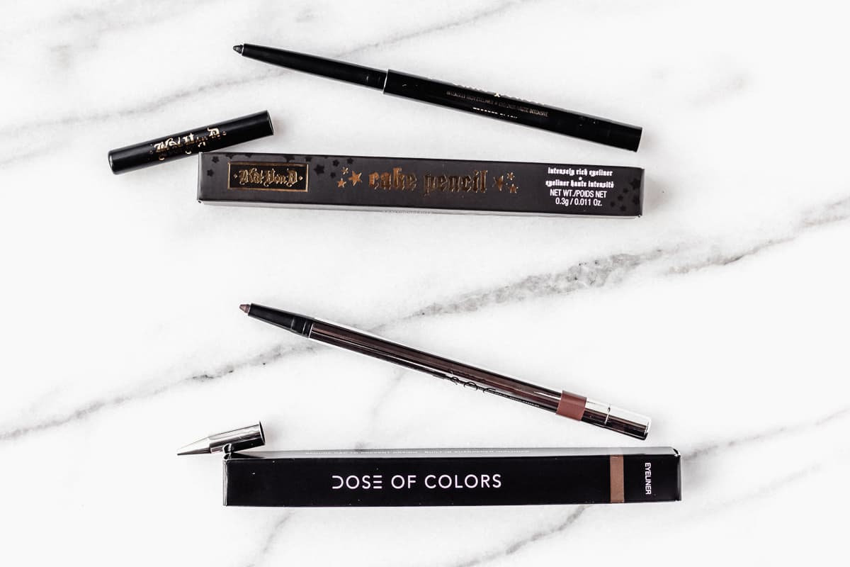 KVD eyeliner and dose of colors eyeliner pencils and boxes on a marble backdrop