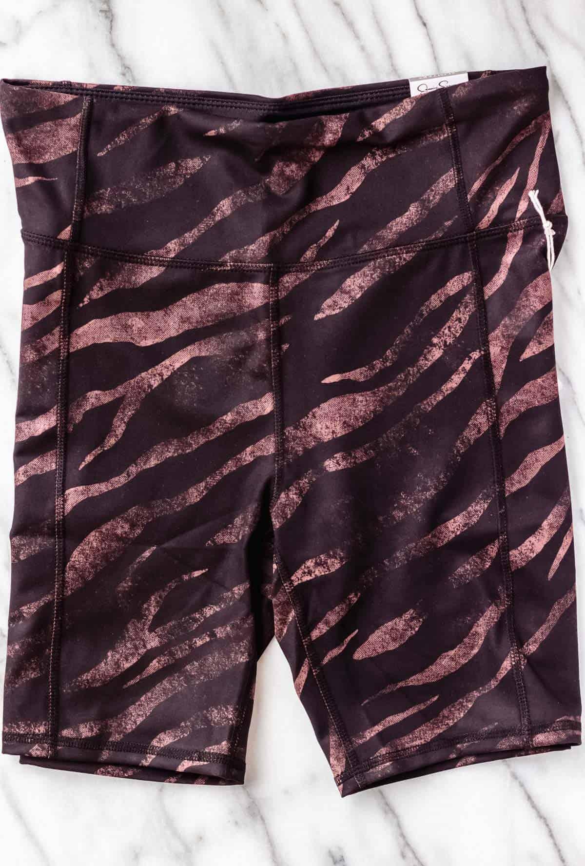 Jessica Simpson Tummy Control Bermuda Shorts in Black Mystic Zebra on a marble background