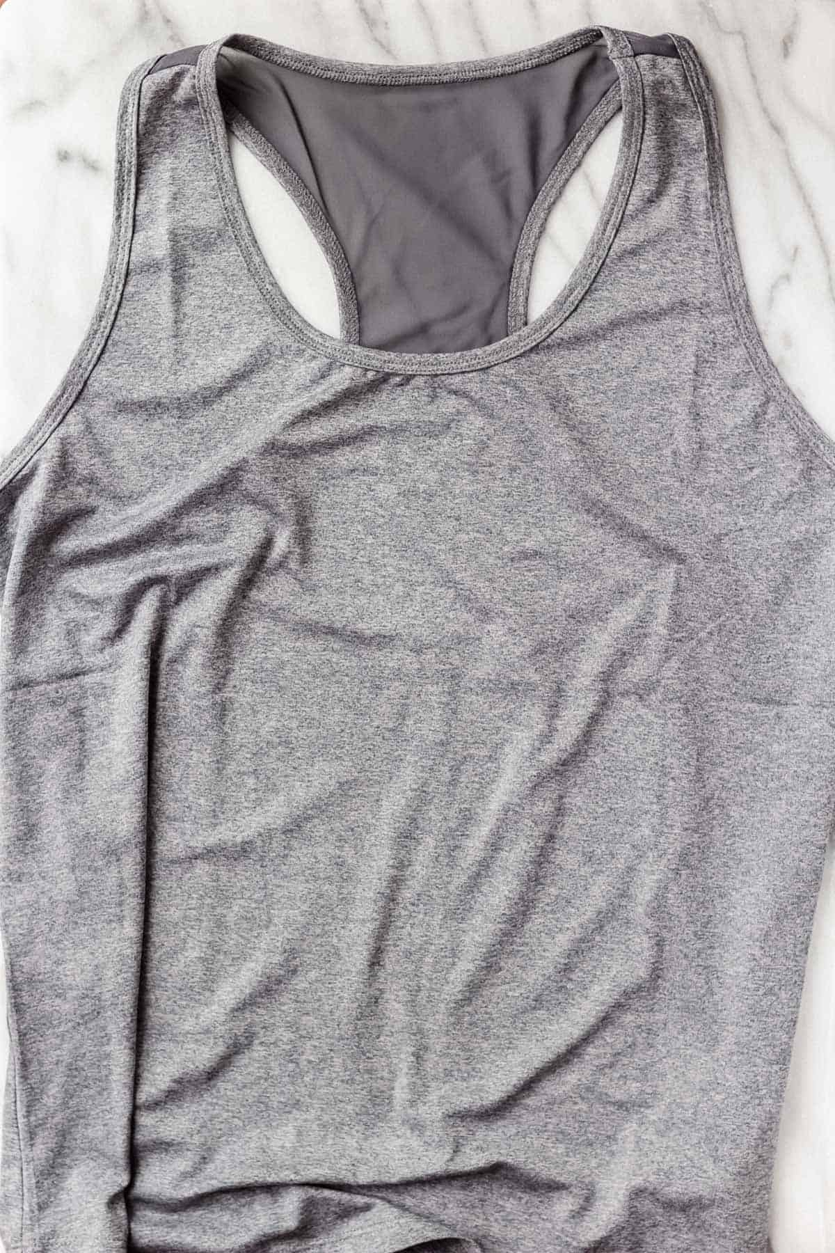 Jessica Simpson Excel Active Tank in Heather Ombre Blue on a marble background