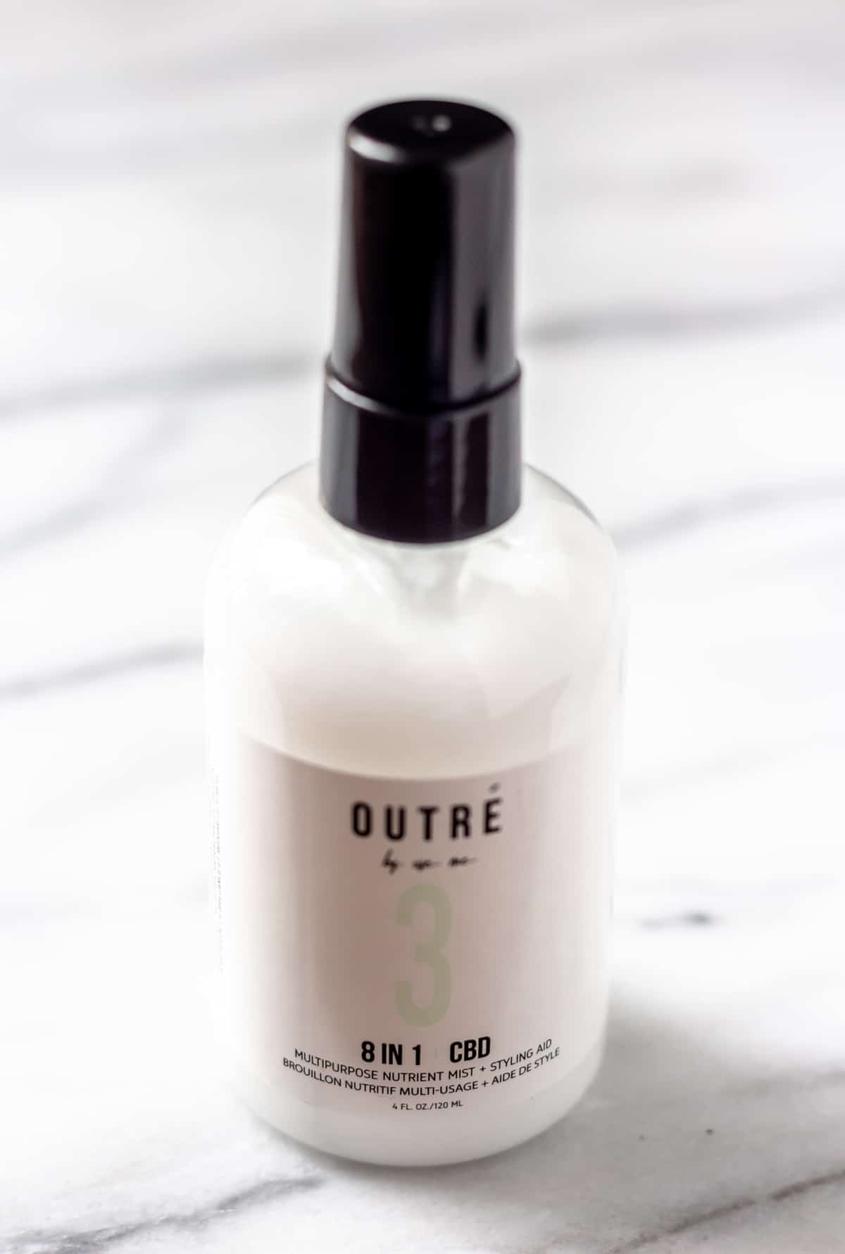 Outre 8 in 1 CBD Leave In Conditioner bottle on a marble background