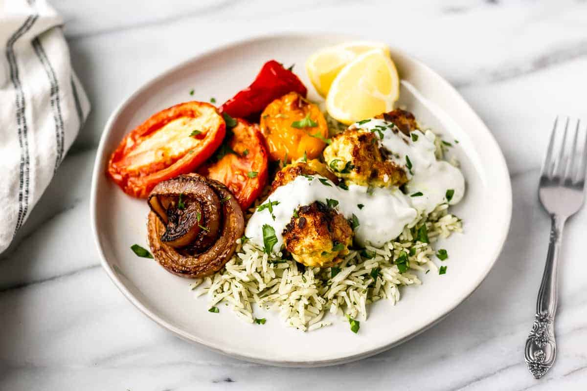 Persian Chicken Koobideh with Herbed Rice & Tzatziki Sauce from gobble on a white plate