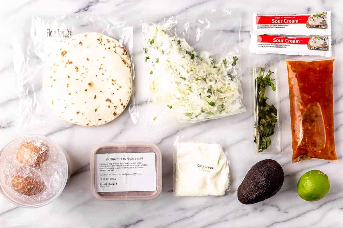 Ingredients to make Huevos Rancheros laid out on a marble backdrop