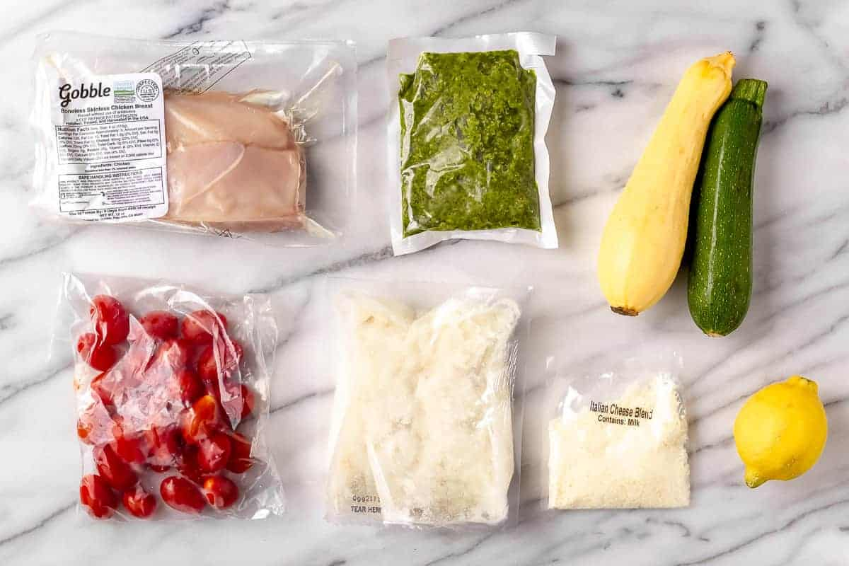 Ingredients need to make Sheet Pan Chicken with Basil Mashed Potatoes & Roasted Zucchini Squash laid out on a marble backdrop