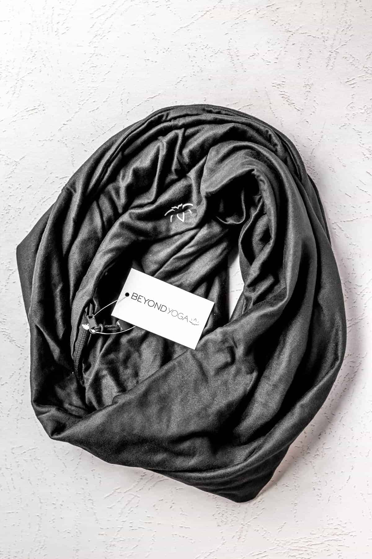 Beyond Yoga Infinity Hidden Pocket Scarf in black on a light background