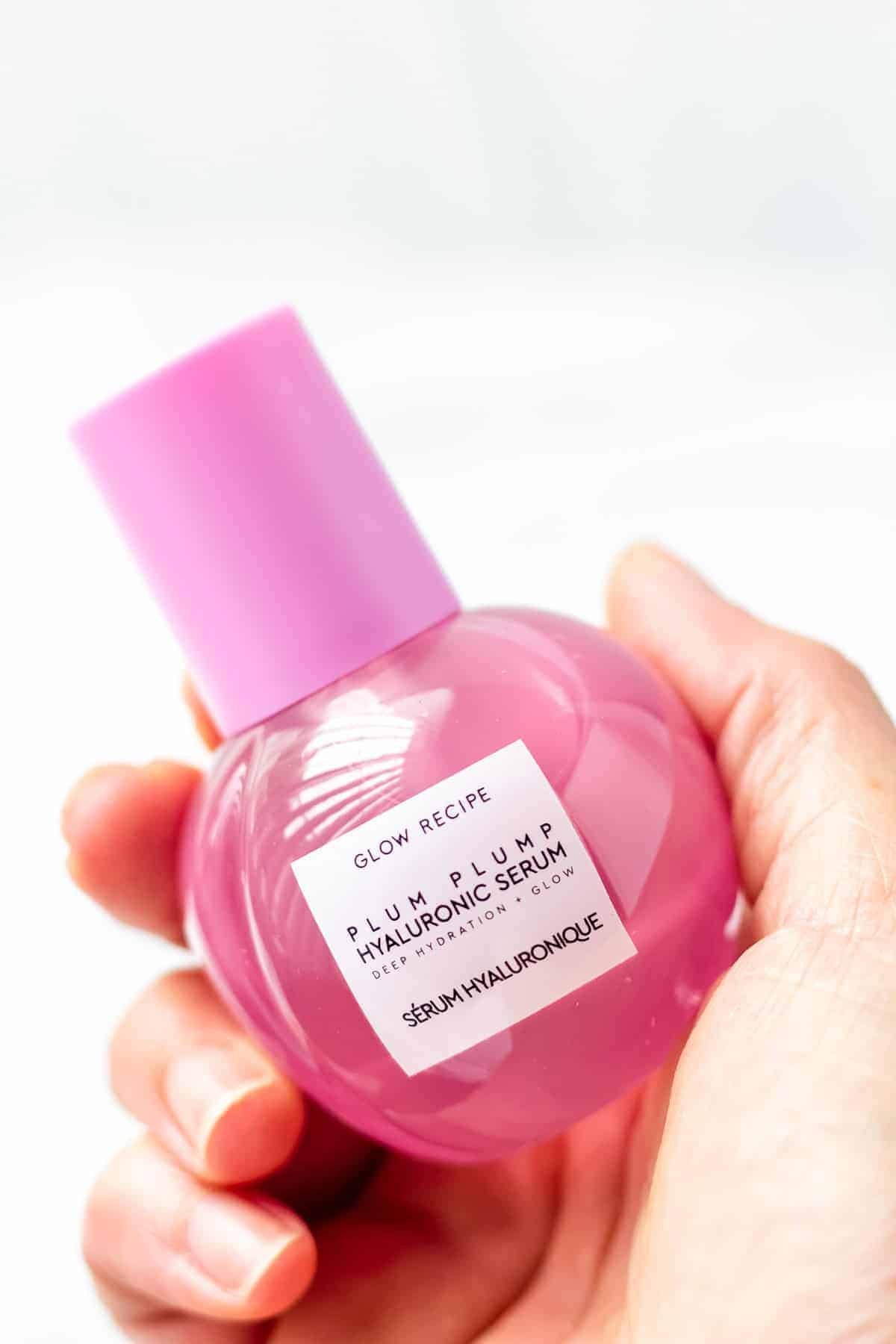 A hand holding a bottle of Glow Recipe Plum Plump hyaluronic serum on a white background.