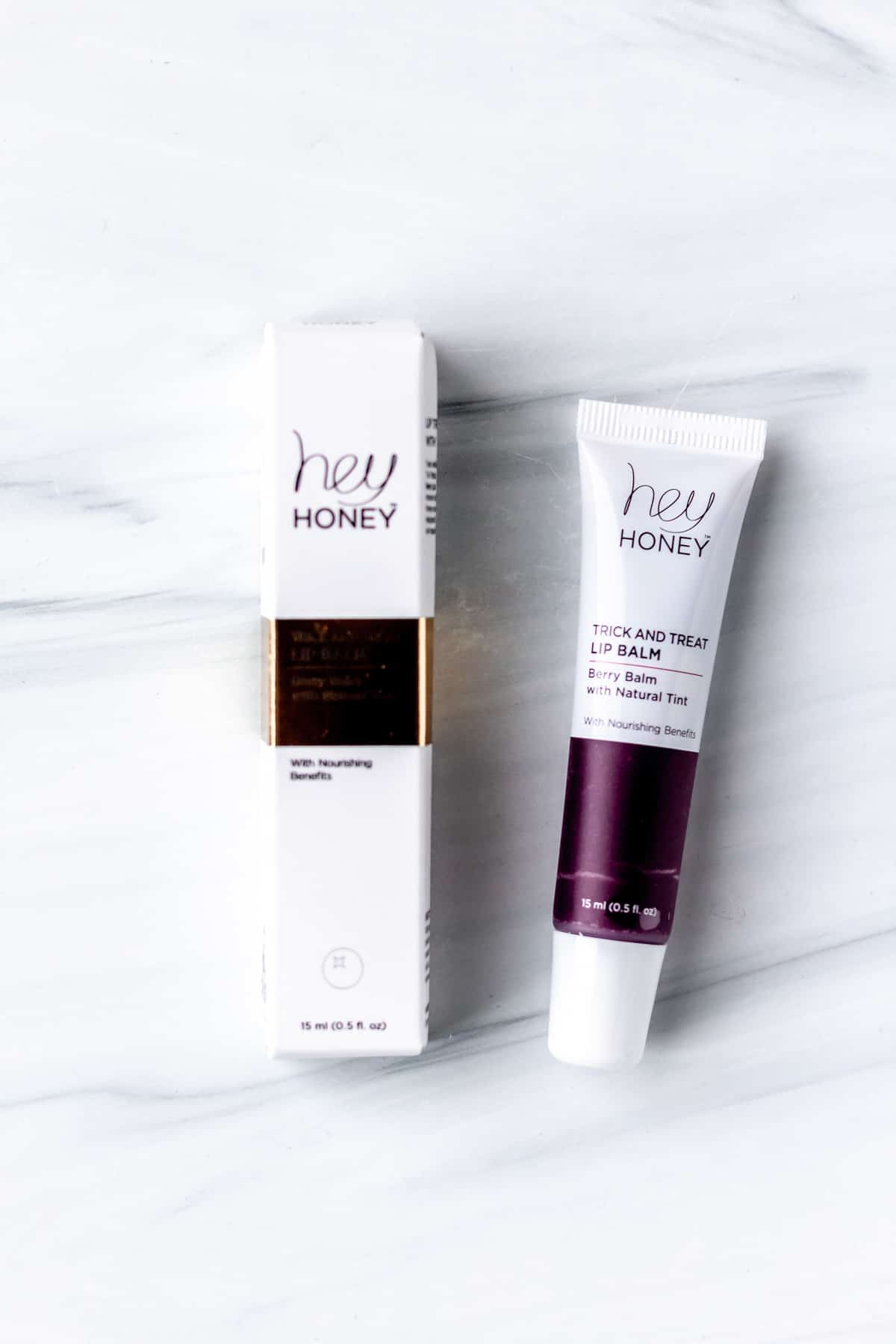 Hey Honey Trick and Treat Lip Balm in Berry Balm next to its box on a white background.